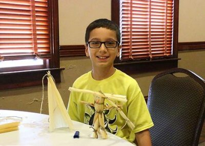 Day 2: Campers learn the pioneer-era craft of making corn-dolls and figures from corn husks.