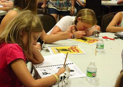 Day 1: Campers work in their activity books provided as part of the 5-day program.